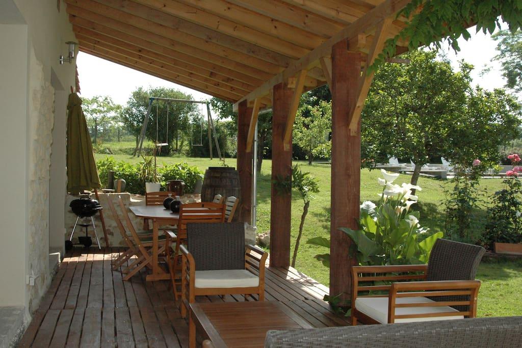Terrasse couverte avec fauteuils, table et chaises, BBQ au charbon de bois