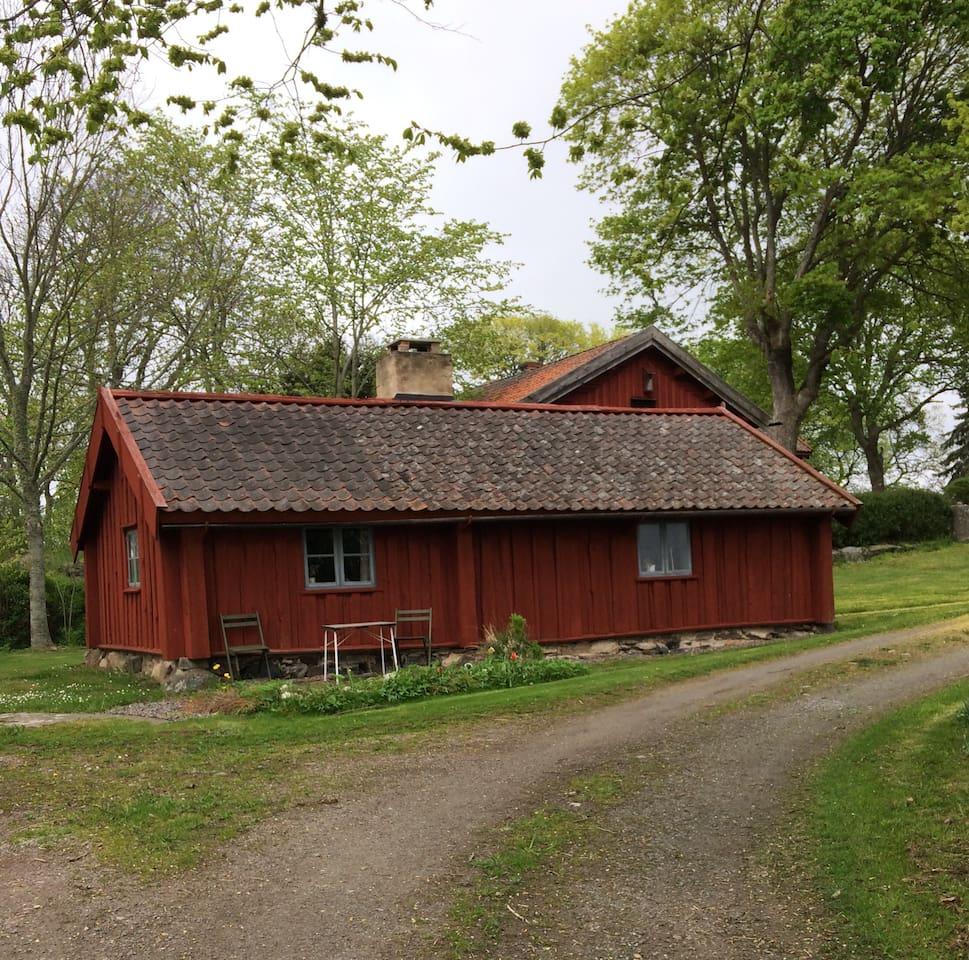 Stugan ligger nära övrig bebyggelse på gården.