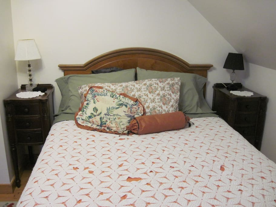 Queen bed with crocheted antique quilt.