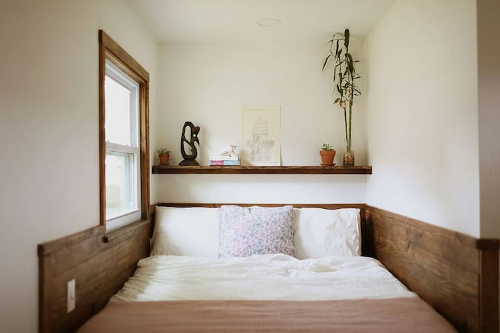 Full size bed with white linens.
