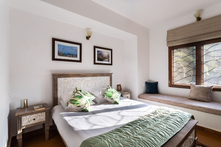 The Second Bedroom is located on the Ground floor with a cupboard, Airconditioner, and En-suite bathroom.  To the left of the bed is a Sitting area near the Window