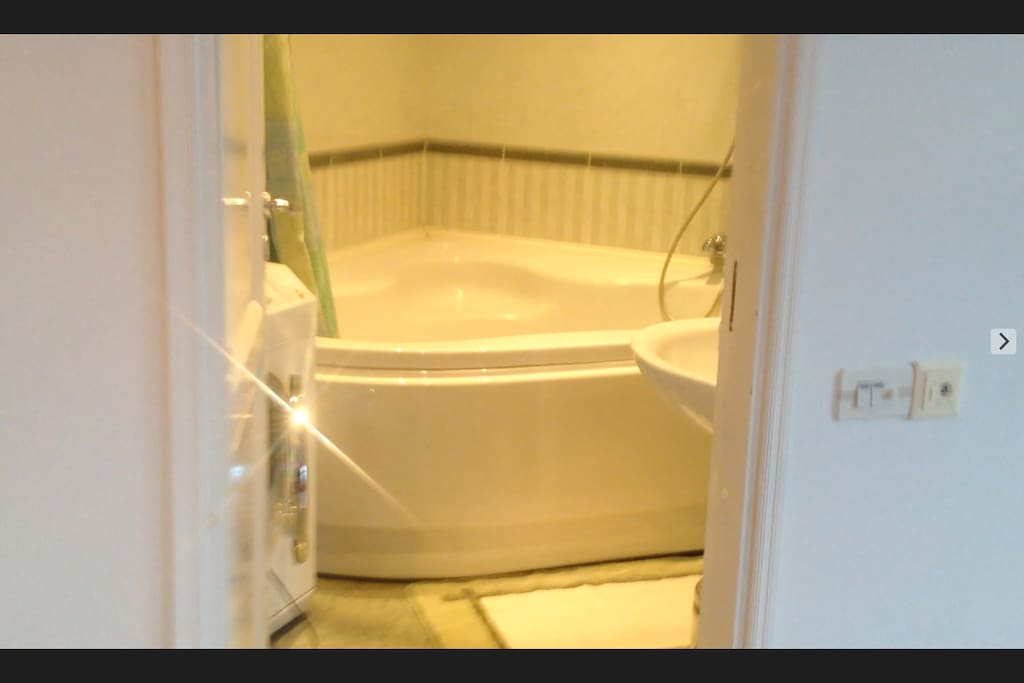 The bathroom with extra large tub and washer machine.