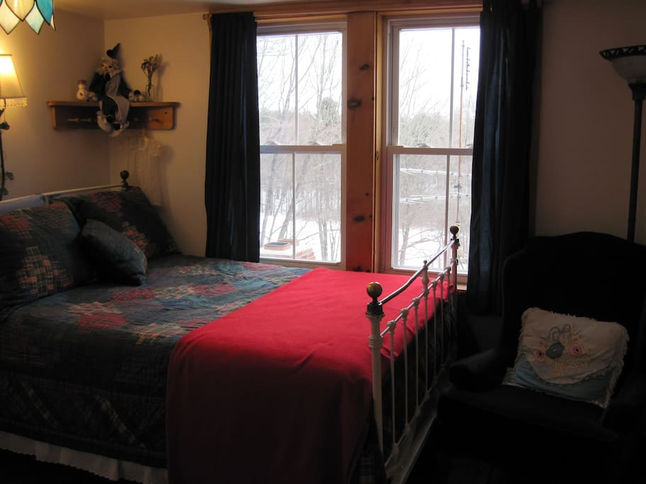 Antique brass and iron bed, hand made quilt. Sunny window view of sheep in the pasture.