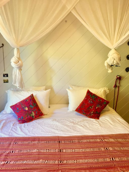 comfortable Kingsize bed in light airy room, with full glass louvres and sliding door, looking out onto the garden