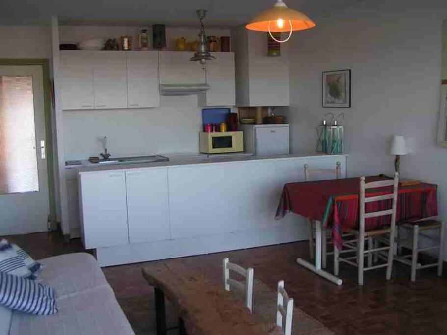 Coin cuisine dans le salon, vue mer, équipements divers : plaques électriques, frigo avec congelateur, grille-pain, micro-ondes, cafetière, bouilloire électrique...