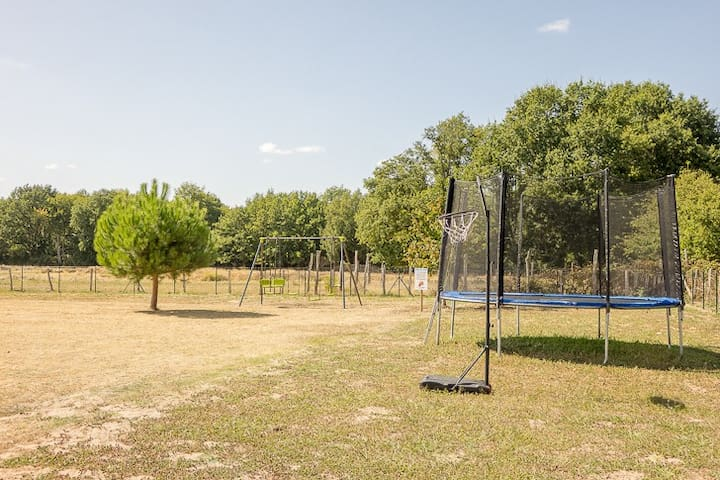 Jardin extérieur entièrement clos & sécurisé pour les enfants, disposant d'un trempoline, d'une balançoire, d'un but de football, d'un panier de basket