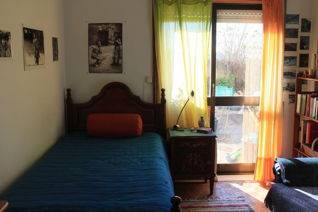 Quarto solarengo, com espaço, mesa, cadeira e sofá, guarda-fatos e cómoda para roupa. Dá para um terraço e jardim.