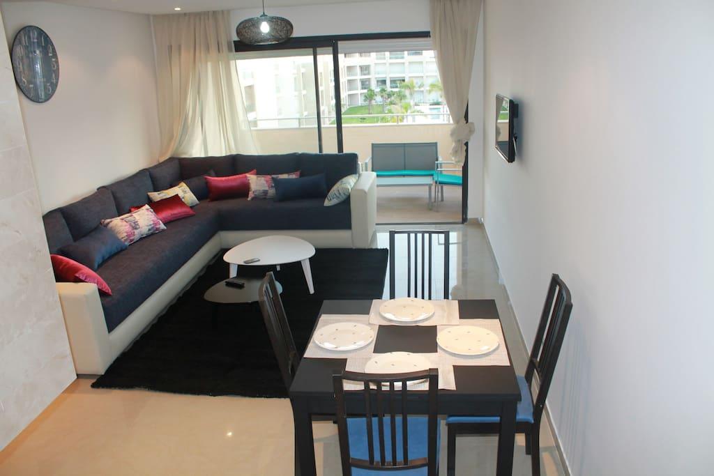 Un grand salon confortable, un coin repas pratique et une belle terrasse ouverte sur les piscines.
