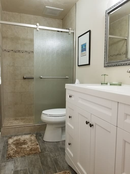Upgraded bathroom with walk in shower, tile floor, vanity and lighting