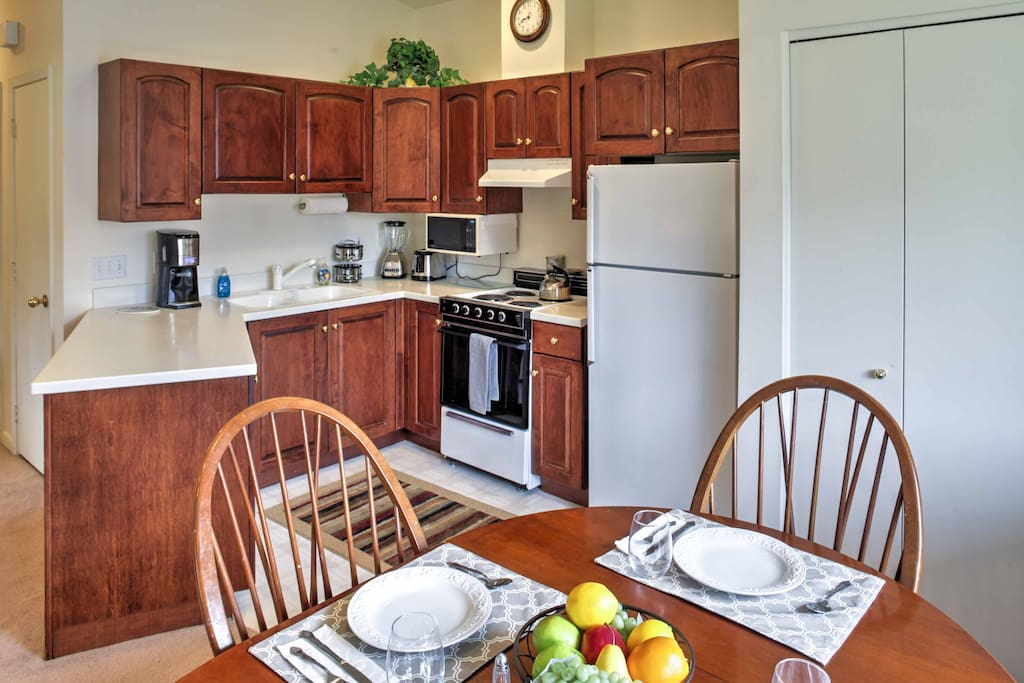The kitchen conveniently opens up to the dining space, where a round table is situated with seating for 4.