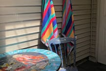 Summer view of your private covered guest porch entrance has extra chairs with sun protectors, beach umbrella tents, beach mats, and a storage cooler on wheels. Sitting chairs and a table...