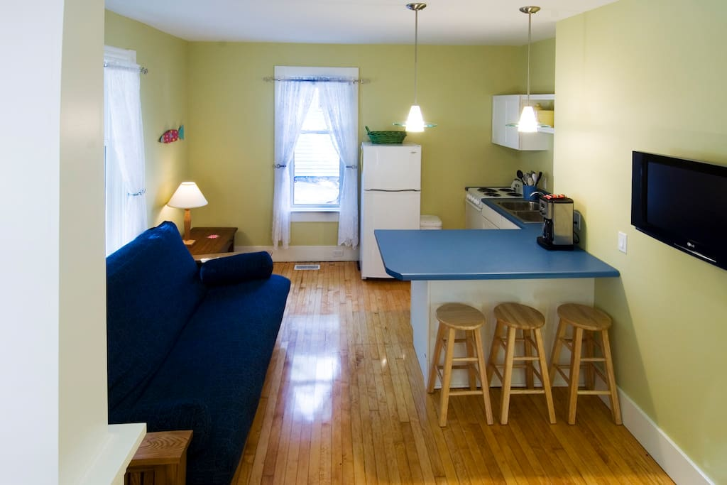 Full kitchen and living area with a queen futon