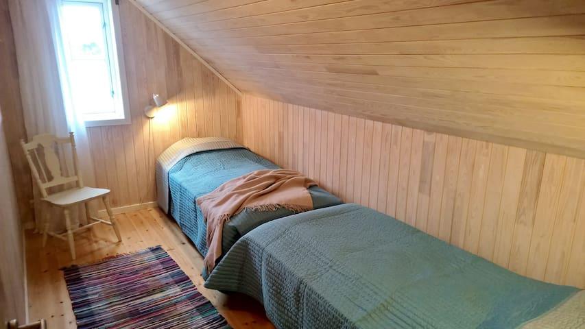 Soverom med to enkeltsenger som enkelt kan gjøres om et dobbeltseng. Utsikt mot fjorden.