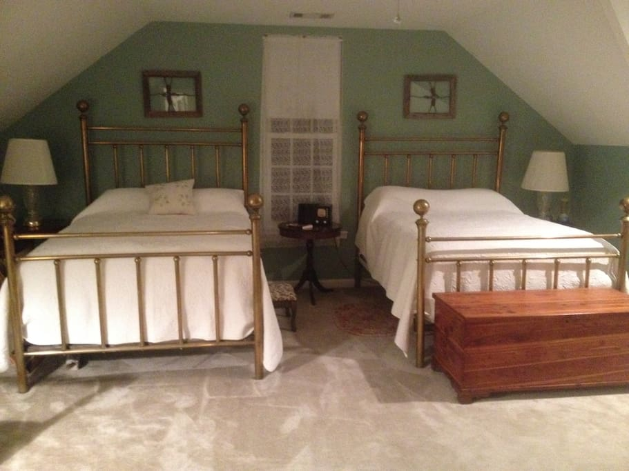 First bedroom with 2 full size antique brass beds for 2 -4 people.