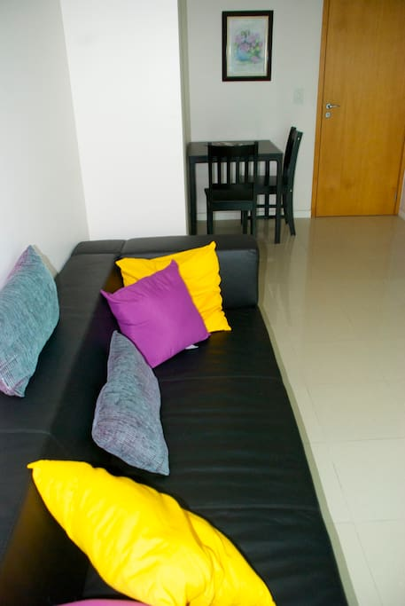 Comfortable couch in living area, with small table and chairs for quick meals