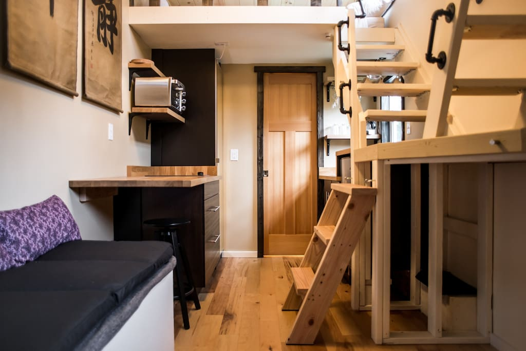 Tiny main space as you walk in. Ladder and stairs up to the two loft spaces on the right