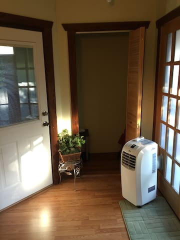 Small walk in closet and portable AC unit for the summer months.