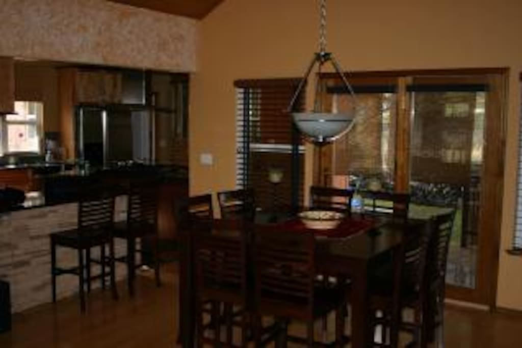 Dining room for 10, 8 at table and two at breakfast bar right next to table. High Cedar Vaulted ceiling and deck off dining area.