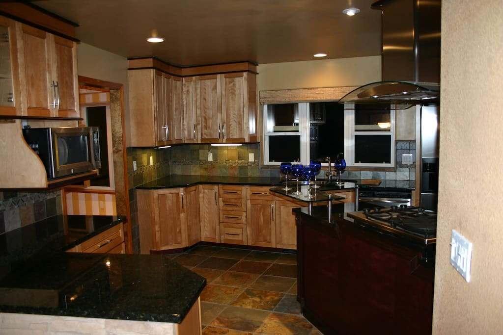 Gourmet kitchen with granite counters and serving stove facing dining for conversation while cooking.