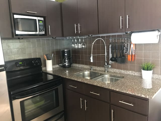 Modern kitchen with all you need to cook, wine glasses, plates, cups, and more.  Granite counter top for a clean look.