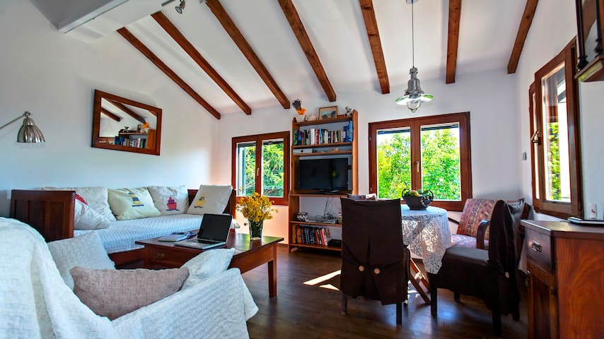 sitting room with high ceilings that are decorated with sloping wooden beams