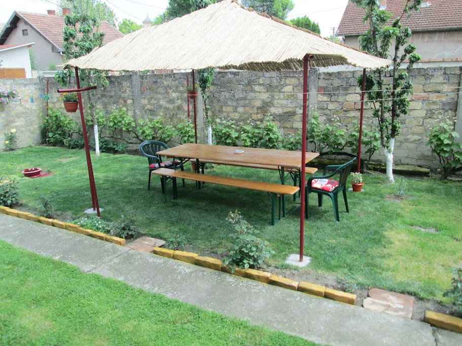 The patio cover with table, benches and chairs
