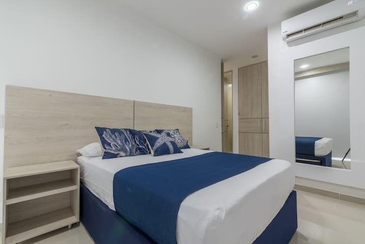 Tercera habitación con baño, aire acondicionado, TV y salida directa al balcón.   Third bedroom with bathroom, air conditioner, TV, and direct access to the balcony.