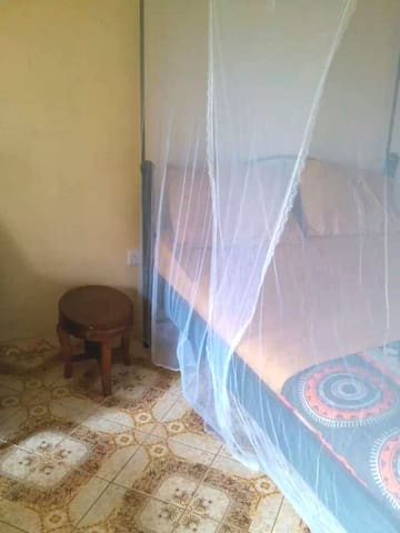 Queen bed, mosquito net and bedside table