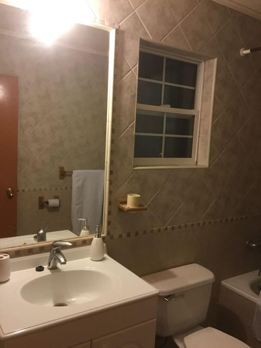 Vista baño compartido, amplio con bañera. Mueble del vanitorio contiene secador de pelo.