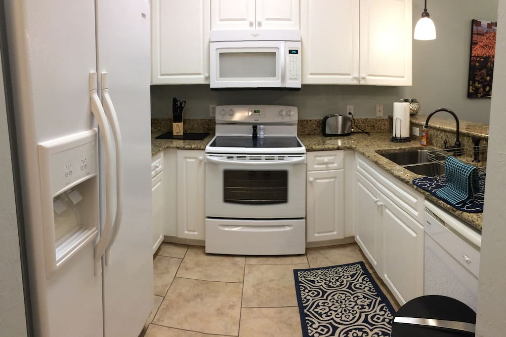 Fully equipped kitchen with granite counters, plenty of storage space, pots, pans, dishwasher, and more.