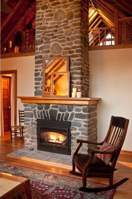 Central (gas-fueled) fireplace with an exposed river stone chimney