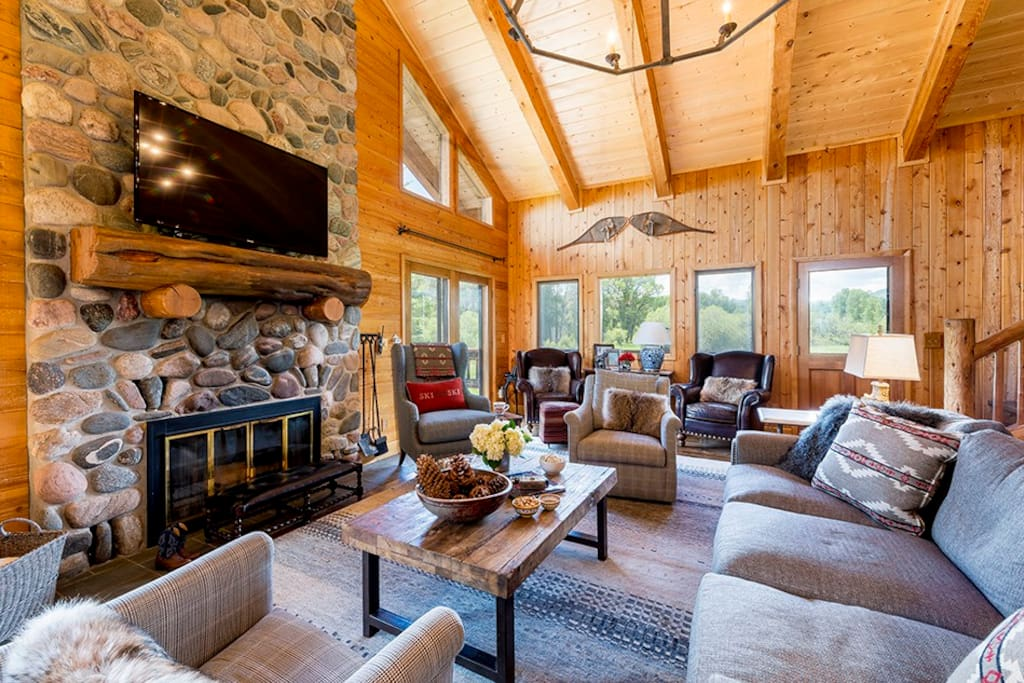 A river rock wood-burning fireplace is the focus of the spacious living room