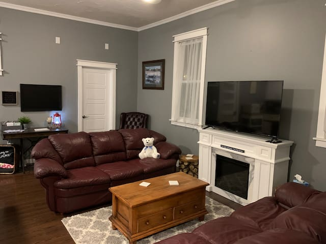 """This is our living room where you will find the electric fireplace and a 55"""" smart tv, complete with a HDMI cable for all your business/entertaining needs. Feel free to log into your own Spotify and Netflix apps."""