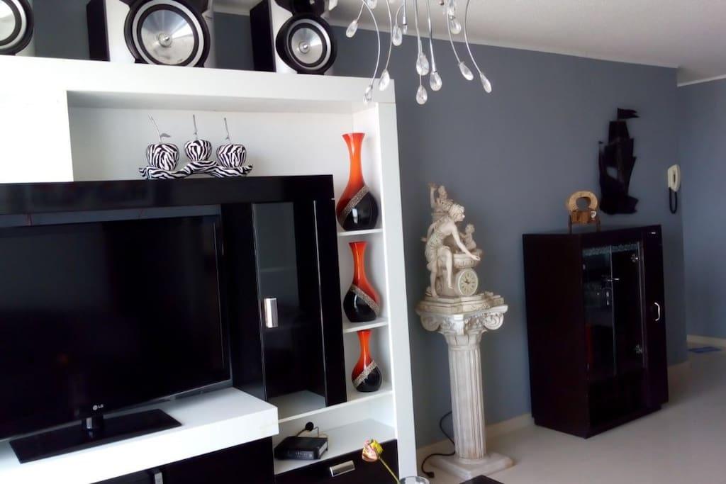 """Sala con sillón completo y tv 47"""" + equipo de sonido, zona bien iluminada. Vista al mar."""