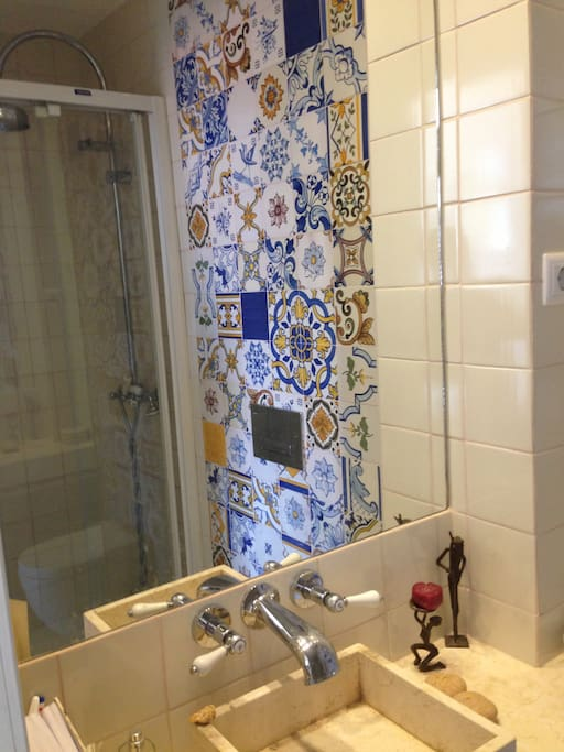 Smaller toilet and shower decorated with a mosiac of the famous portuguese tiles (Viuva Lamego)