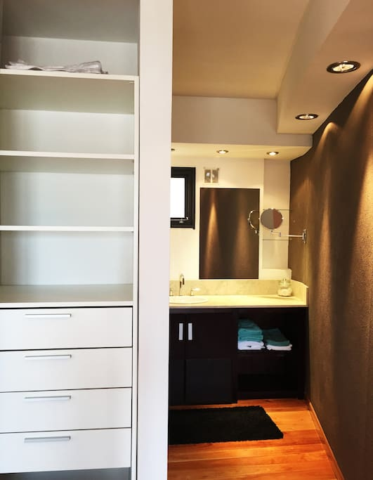 Ensuite bathroom with built-in cabinets and closet