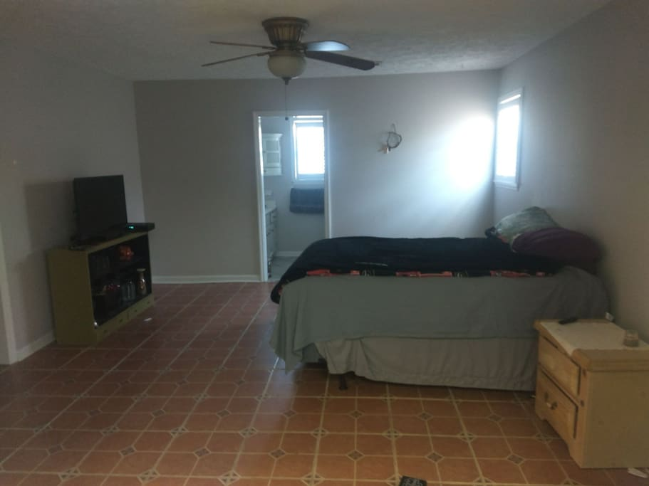 Master bedroom with a queen plus size bed with a private bathroom and shower