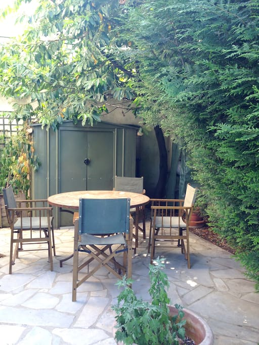 Terrasse avec salon de jardin et barbecue.