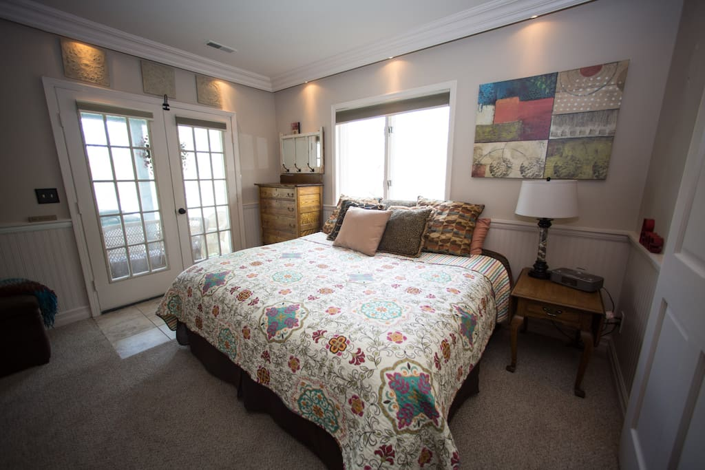 """Kingsize bed and dresser in living room suite (couch, 50"""" TV, dining area). French doors lead to patio."""