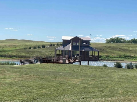 Unique cabin over water on prairie.