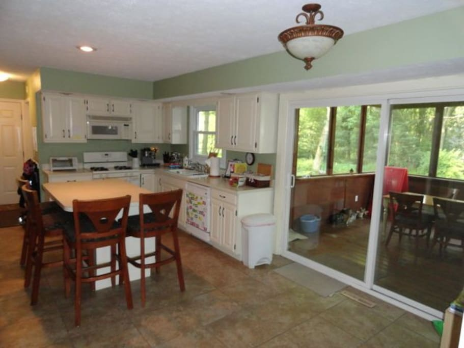 Full kitchen with appliances connected to covered patio
