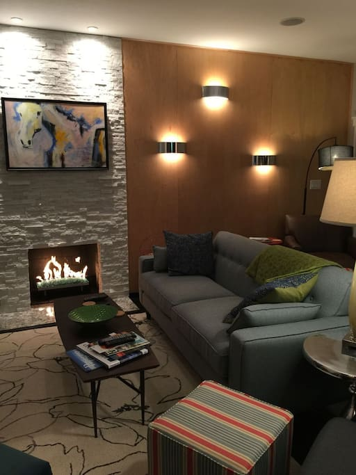 The deluxe living area features a glass rock fireplace, custom furnishings and decor, and original art.