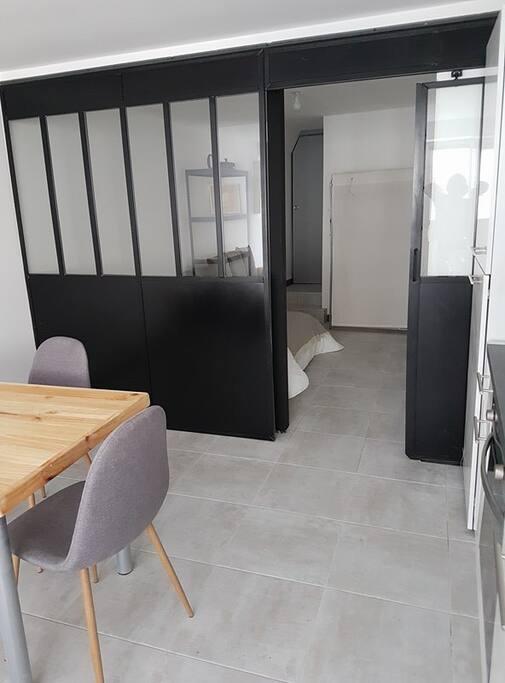 Cuisine  à droite, salle à manger à gauche, chambre séparé par une verrière et porte coulissante