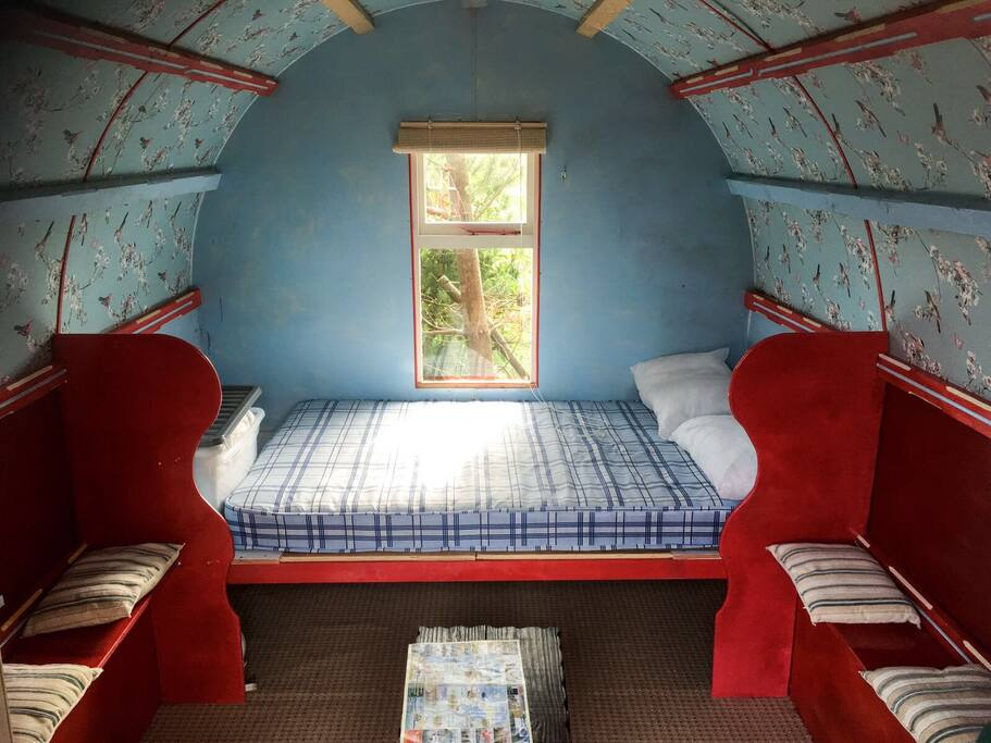 Inside the gypsy caravan - double bed and seating area