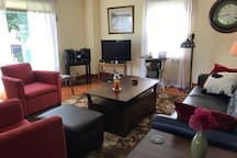 The main living room has comfortable seating, a TV, and stereo