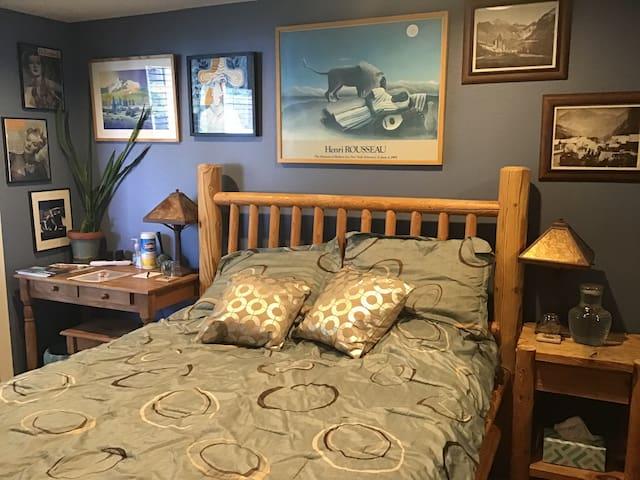 Guest bedroom features queen bed, desk...