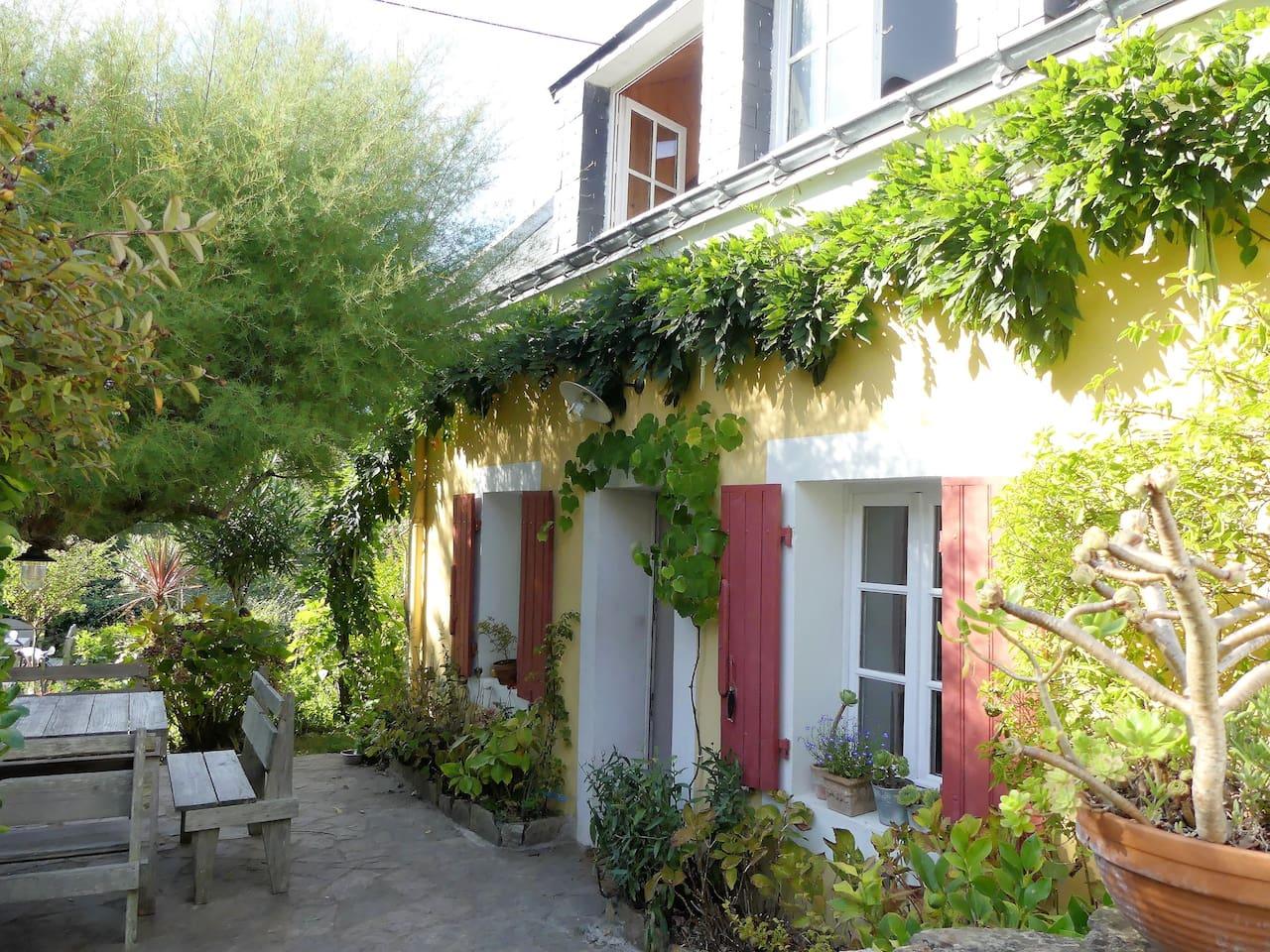 Entrée de la maison et terrasse avec grande table extérieure