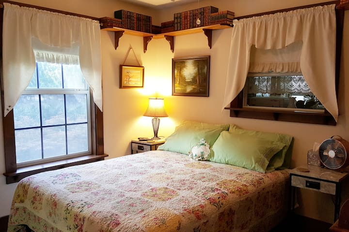 Queen bed with 4 pillows, reading light, overhead light and fan, and personal fan. Blackout shades on both windows.