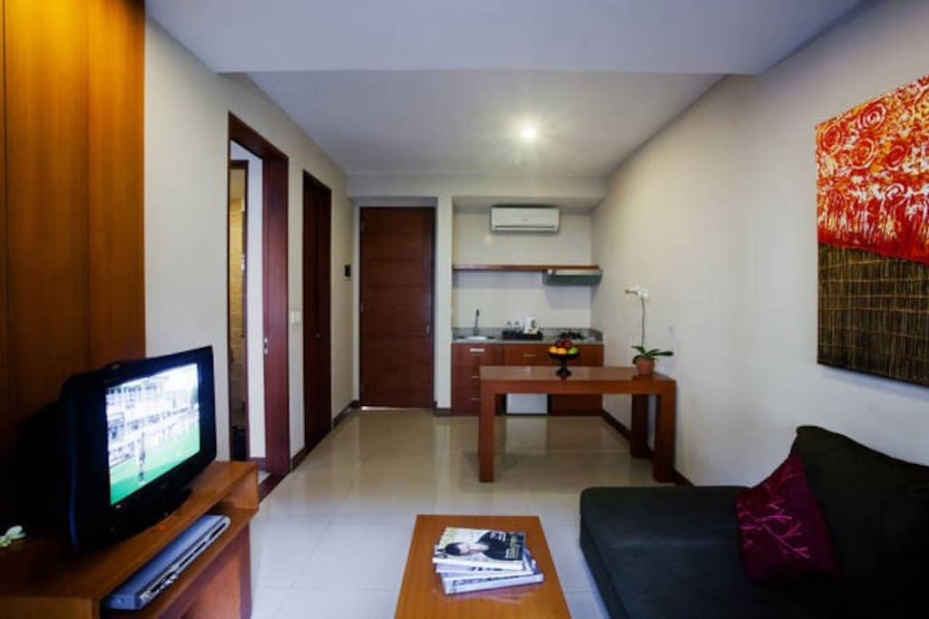 your private living room with TV and small kitchen with dining table
