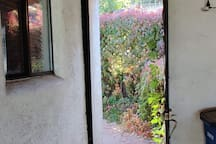 Doorway at end of carport leads to back patio and entrance to the studio.